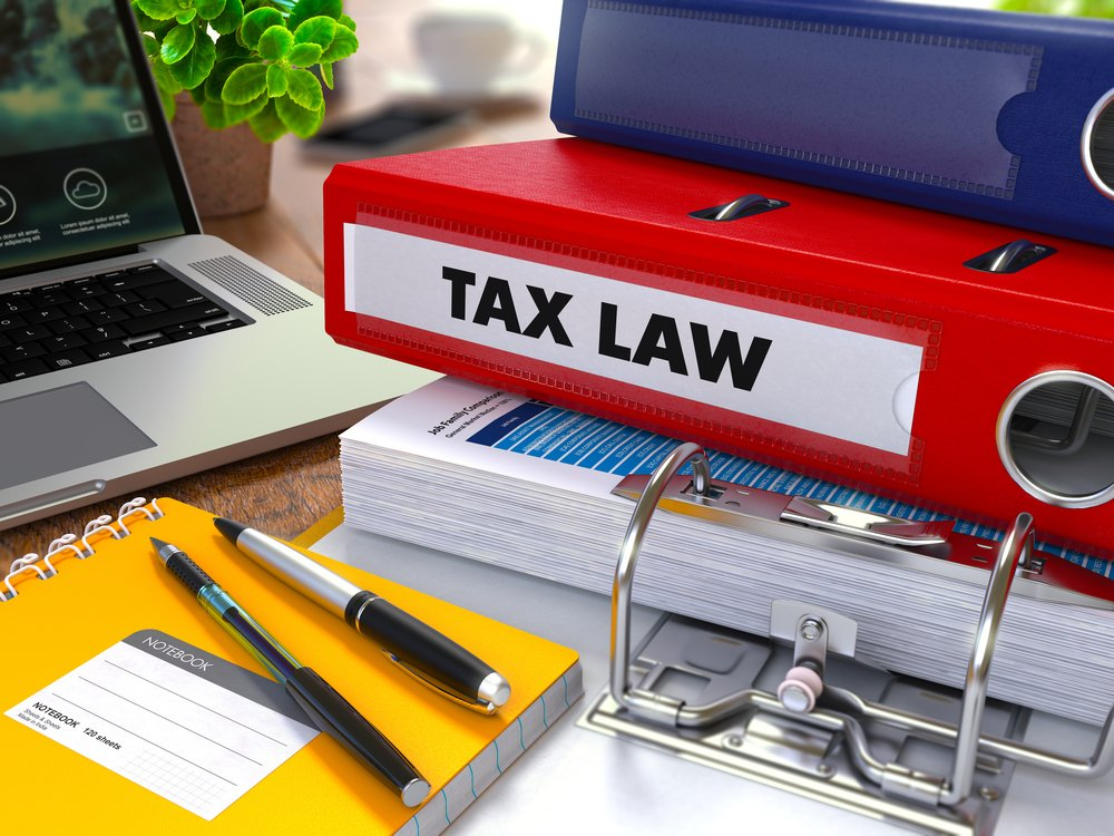Red Ring Binder with Inscription Tax Law on Background of Working Table with Office Supplies, Laptop, Reports. Toned Illustration. Business Concept on Blurred Background. 3d Render.